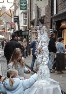 Ice sculpture with children looking on